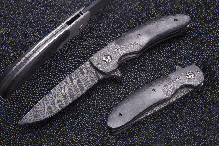 """""""SOLD"""" The Vanguard. Fitted with 3 3/8 """"Sonic Wave"""" Damascus blade, by Mike Norris, and Damascus bolsters, carbon fiber scales, and mosaic pattern Damascus backspacer. Click on image to view in high resolution."""